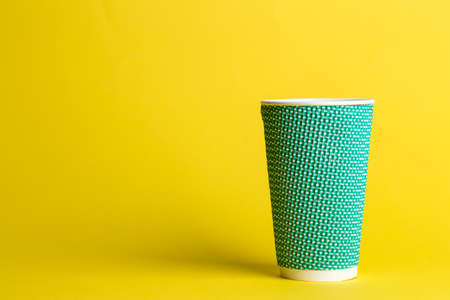 coffee to go in a disposable cup on a yellow background, place for text