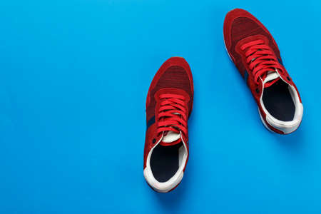 red mens sneakers on a blue background. casual shoes are out of fashion. place for text Stock Photo