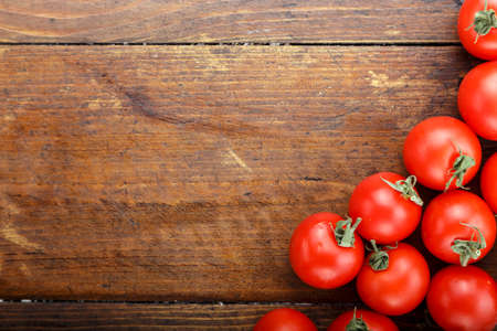 tomatoes on a wooden background lie in the corner. place for text Stock Photo