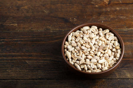 salted peanuts in a clay plate on a wooden background. place for text