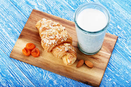 Fresh croissant and a glass of milk on the table. Traditional French breakfast