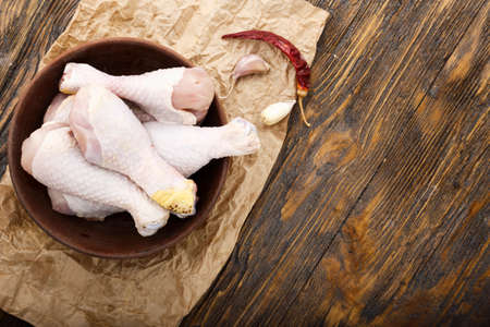 raw chicken legs and spices on a wooden table on kraft paper Banque d'images