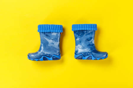 a pair of blue rubber boots on a baby boy on a yellow background. autumn shoes
