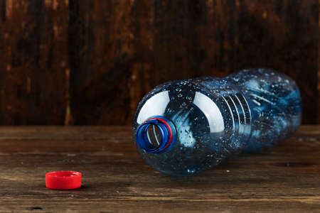 empty plastic bottle lies on a wooden background. place for text. plastic recycling