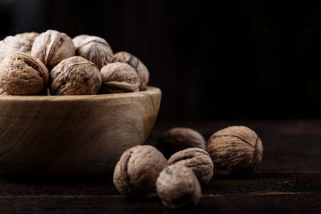 inshell whole walnuts on dark wooden background. in a wooden plate Фото со стока