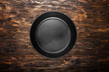 empty clean cast iron skillet on a wooden background.