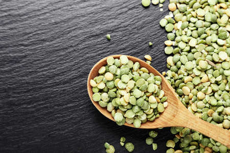 dry green peas scattered on a black background.