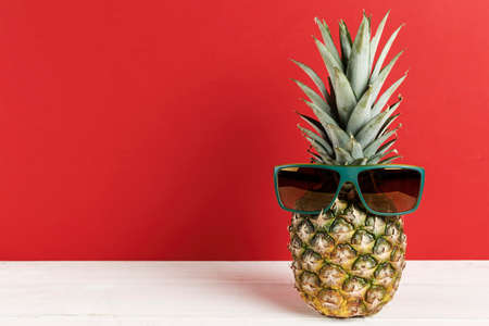 Pineapple in sunglasses on a bright background. tropical fruit space for text Imagens