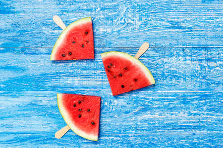 triangular slices of watermelon on a stick on a shabby blue background