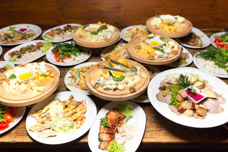 many plates of food on the holiday table. cold appetizers and salads in the restaurant Stock Photo