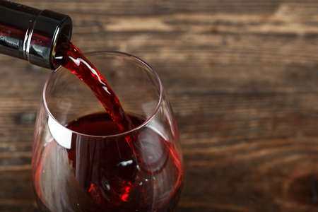 in a glass pour red wine, on a wooden background, space for text 스톡 콘텐츠