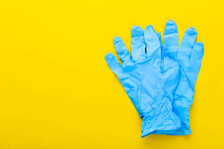 New sterile blue medical gloves lie on a yellow background. space for text