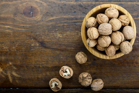 harvested walnuts in shell on wooden background. space for text