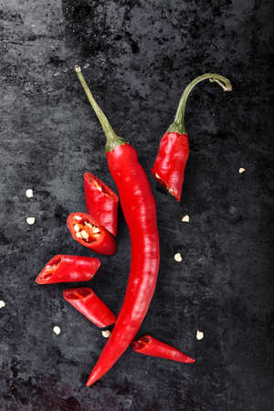 hot red pepper sliced and whole on a black background. space for text