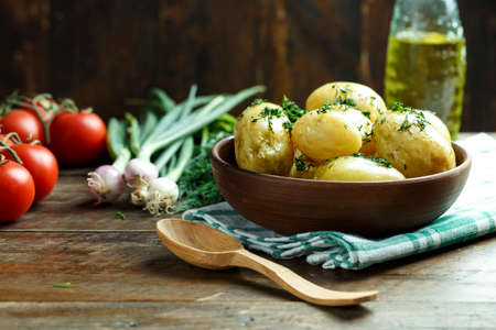 boiled baby potatoes with dill in a plate. summer country lunch nearby are raw vegetables. space for text