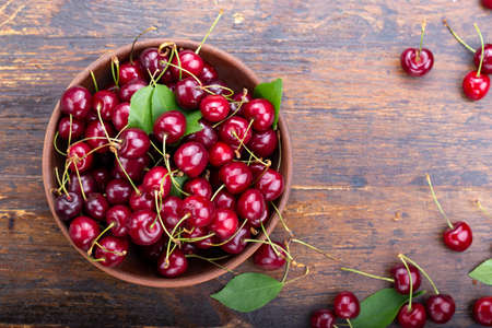 sweet red cherries in a plate on a wooden background. space for text