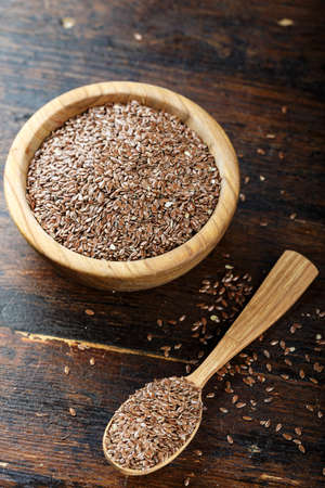flax seeds in a wooden plate on a brown wooden background. space for text