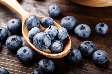 Fresh blueberries in a wooden spoon on a wooden table, closeup. space for text 스톡 콘텐츠