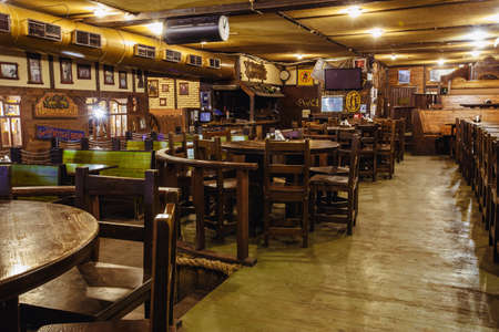Kiev, Ukraine-March 19, 2018. Traditional Irish beer pub with a wooden interior. many empty tables and chairs.