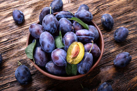 ripe plums in a crop plate on a brown wooden background. space for text Stock Photo