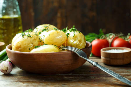 boiled fresh potatoes with dill. fresh summer lunch in a plate. next to fresh vegetables