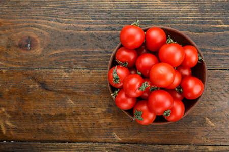 Pomodori freschi in un piatto su un fondo di legno. Raccolta di pomodori. Vista dall'alto Archivio Fotografico