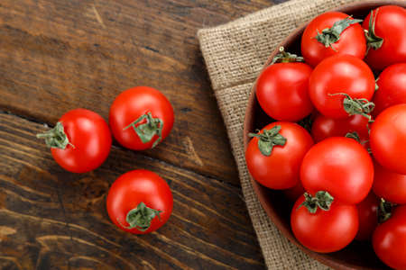 Fresh tomatoes in a plate on a wooden background. Harvesting tomatoes. Top view