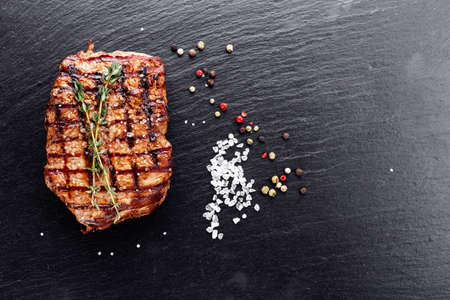 Cooked steak with seasonings and sauces on a slate board Stock Photo