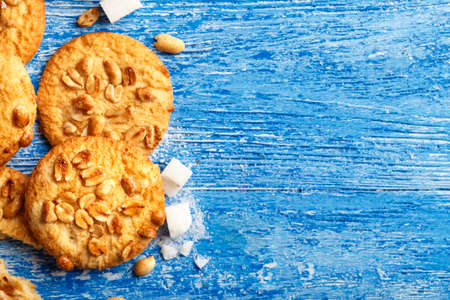 homemade fresh cookies with peanuts on a wooden background, pieces of sugar are lying next to, place for text