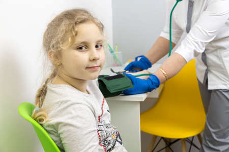 The doctor measures the blood pressure of the child with a tonometer. preventive measures