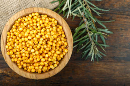 Sea buckthorn in a wooden plate, on a brown wooden background, space for text  Imagens