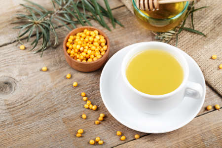 fresh sea buckthorn tea on a simple wooden background in a small plate. curative vitamin drink for winter