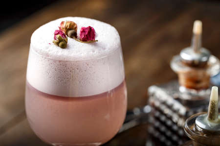 Pink alcoholic cocktail with foam, decorated with dry roses. drink on wooden background. bartender attributes are next to each other. nightlife in a big city Imagens