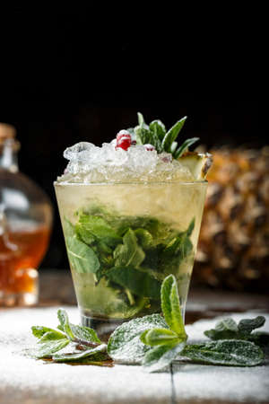 refreshing mojito cocktail with ice and mint in a glass on a wooden rack. cocktail decorated with cranberries