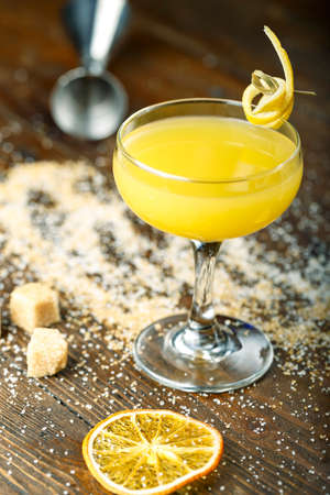 beautiful yellow alcoholic cocktail, decorated with orange peel. on a brown wooden background. sugarcane is scattered nearby and a lemon is lying