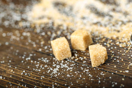 cane sugar scattered on a brown wooden table - in the form of granulated sugar and in the form of cubes