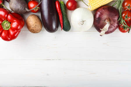Fresh summer vegetables laid out in a row on a white wooden background. space for text
