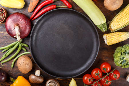Fresh summer vegetables laid out in a row on a brown wooden background. place for text - on a cast iron skillet in the center