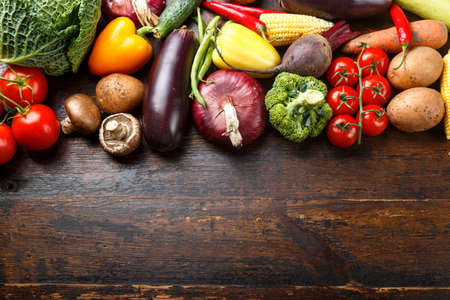 Fresh summer vegetables laid out in a row on a wooden background. space for text