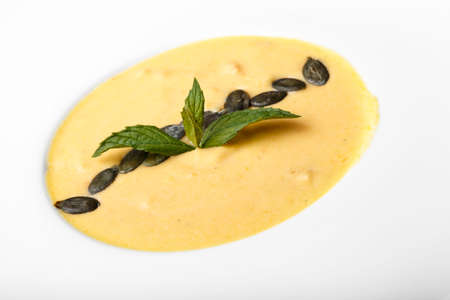 pumpkin cream soup in a white plate. On a soup are beans pumpkin and basil leaves. top view