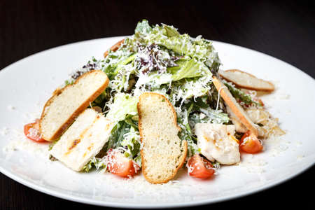 Traditional Caesar salad with chicken, bacon, lettuce letuk, croutons, onions, tomatoes, sprinkled with parmesan cheese.