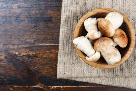 uncooked boletus mushrooms in a plate on a brown wooden background. the plate is on a napkin of burlap