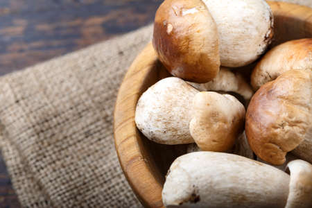 uncooked boletus mushrooms in a plate on a brown wooden background. the plate is on a napkin of burlap, the knife is next
