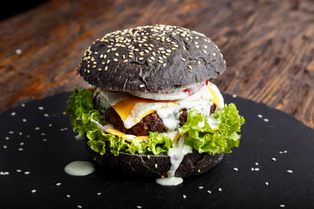 black burger with beef cutlet with vegetables, sesame seeds, on slate board on wooden background