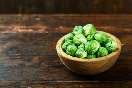 raw brussels sprouts in a wooden plate, on wooden background. place for text