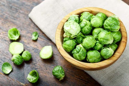 raw brussels sprouts in a wooden plate on a burlap napkin, on wooden background. place for text