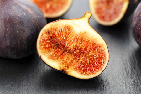 whole and sliced ripe fresh figs on a black table. close-up. the fruit texture is clearly visible Banque d'images - 129475704