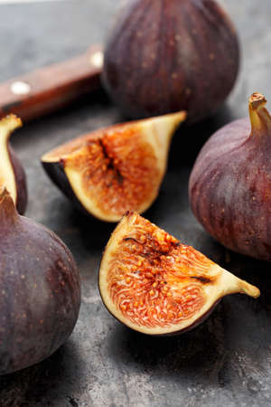 whole and sliced ripe fresh figs on a black table. close-up. the fruit texture is clearly visible Banque d'images - 129475709