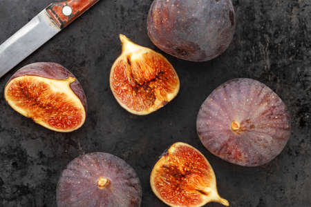 whole and sliced ripe fresh figs on a black table. close-up. the fruit texture is clearly visible Banque d'images - 129475707
