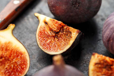 whole and sliced ripe fresh figs on a black table. close-up. the fruit texture is clearly visible Banque d'images - 129475712